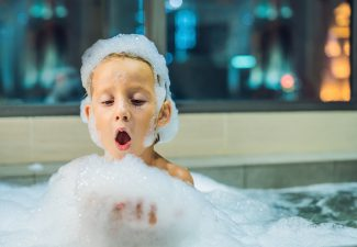 Happy little baby boy sitting in bath tub in the evening before going to sleep on the background of a window overlooking the evening city. Portrait of baby bathing in a bath full of foam near window